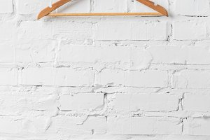 one brown wooden hanger on white wal