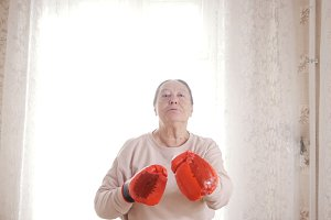 An old senior woman boxing in red