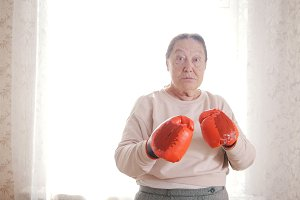 An old senior women boxing in red