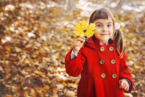 child in a red coat with autumn leav