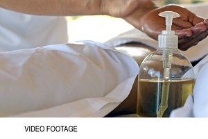 Massage therapist using oil during
