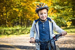 Kid boy on bike in the autumn park.