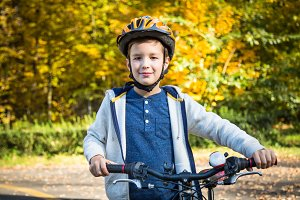 Kid boy on bike in the autumn park.
