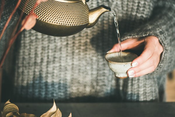 Woman pouring tea from golden teapo…