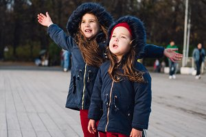 Two young girl having fun in park