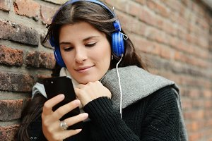 Young woman listening music and usin