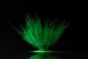 green holi powder explosion on black