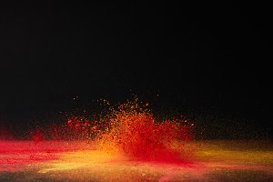 orange holi powder explosion on blac