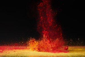 orange holi powder explosion on blac