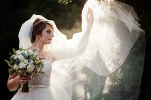 Young bride posing with veil outdoor