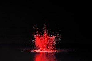 red holi powder explosion on black,