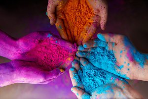 cropped view of hands with holi powd