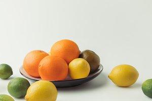 Citrus fruits on plate on white back