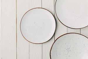 Ceramic glazed plates on white woode