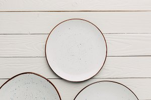 Empty ceramic plates on white wooden
