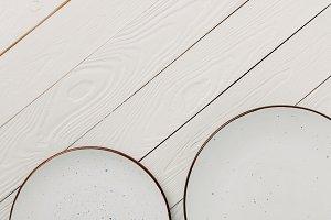 Empty glazed plates on white wooden