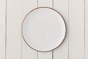Ceramic glazed plate on white wooden