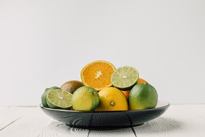 Ripe citrus fruits on plate on white