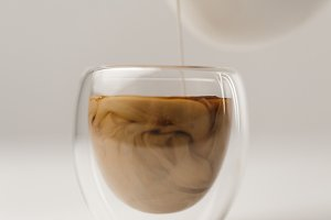 Adding milk to cup with coffee on wh