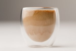 Glass cup filled with coffee with mi