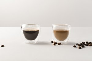 Two cups with coffee on white backgr