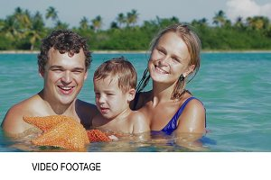 Parents and son in sea water holding