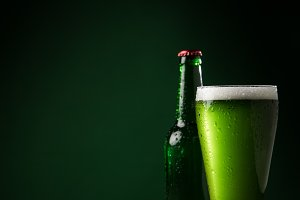 glass bottle and glass of green beer
