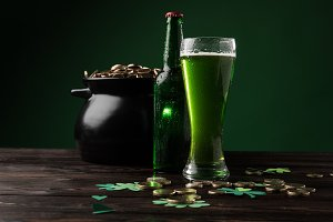 pot with coins and green beer on tab