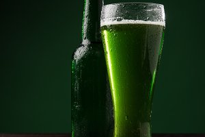glass of green beer and bottle on ta