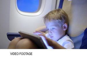 Bored or tired boy in plane using