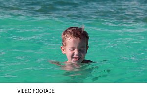 Little boy bathing in clear blue sea