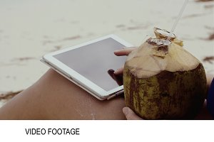 Woman using touch pad having coconut