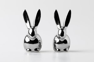 two statuettes of easter rabbits on