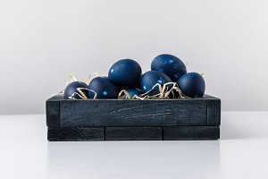 blue painted easter eggs in box with