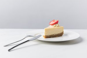 Cheesecake with piece of fresh straw