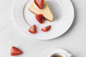 Coffee cup with cheesecake and slice