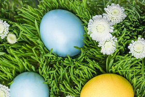 Three painted easter eggs on lawn wi