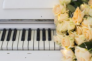 Peach roses with garlands on a piano