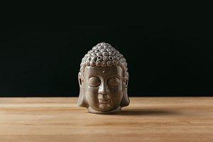 Sculpture of buddha head on wooden t