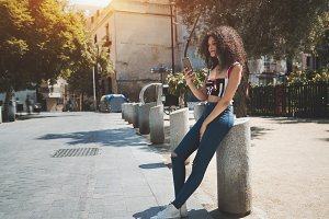 Curly Brazilian girl with cellphone