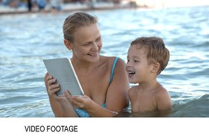 Mother with pad shows his son photo
