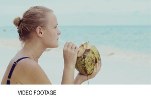Woman beach drinking from coconut