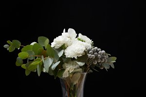 Vase with flower bouquet on table on