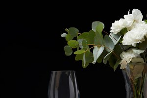 Flowers in vase with empty glasses o