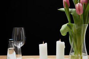 Vase with flower bouquet and candles