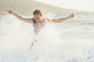 Young woman enjoying splash of wavy