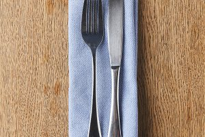 Fork and knife on napkin on wooden t
