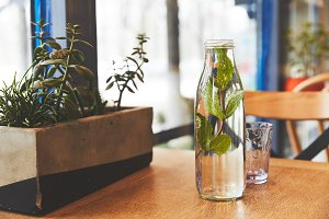 Bottle with mint water and glass on