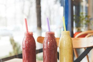 Bottles with assorted smoothies on w