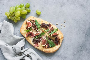Pizza with figs, grapes, ham, greens